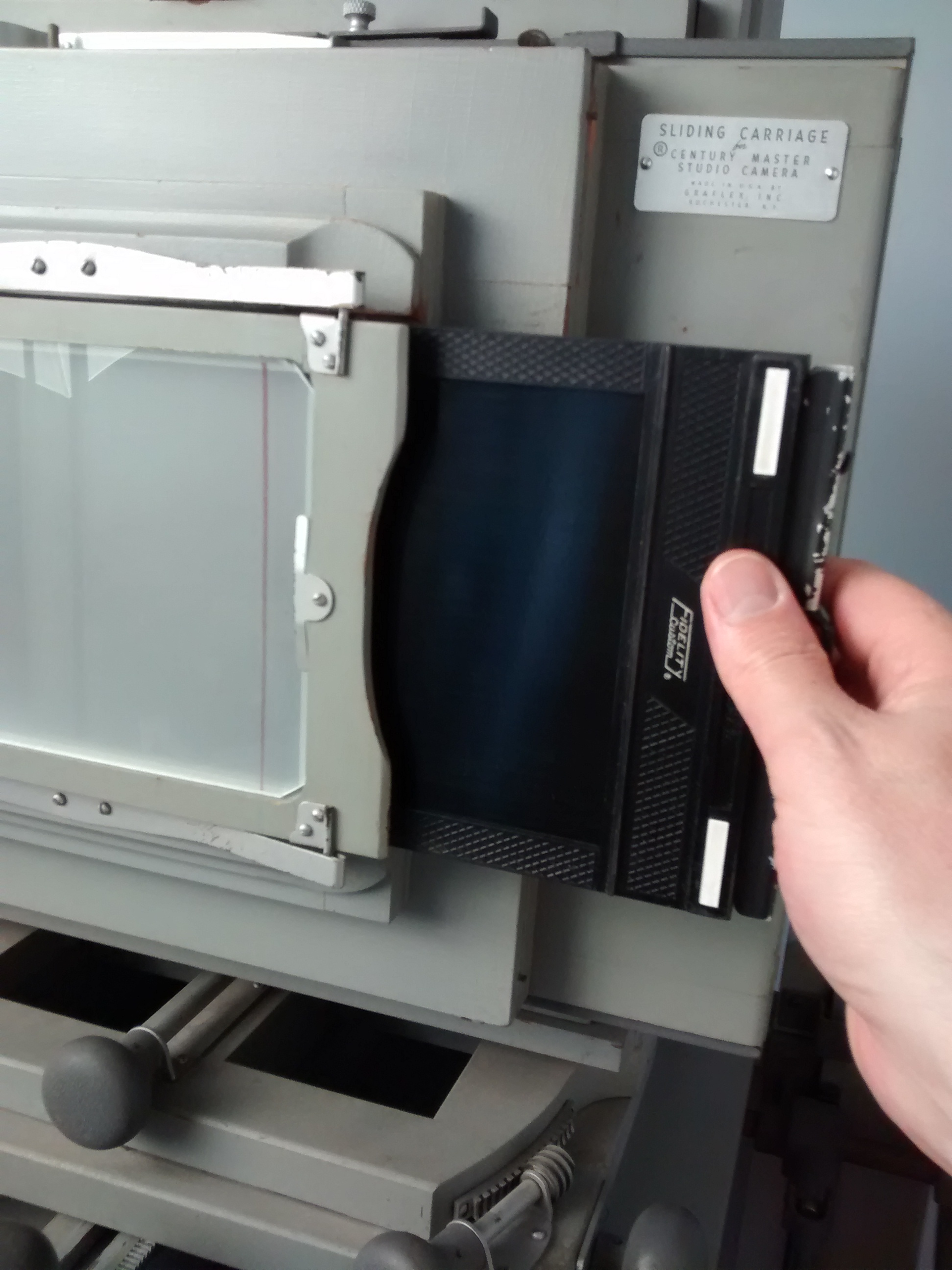 Inserting a 5x7 inch sheet film holder into the spring back of a Graflex Century Master Studio Camera
